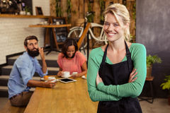 Waitress standing with arms crossed. In a cafe Royalty Free Stock Images