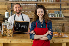 Waitress standing with arms crossed at counter in café. Portrait of waitress standing with arms crossed at counter in café with waiter holding open sign board Stock Photography