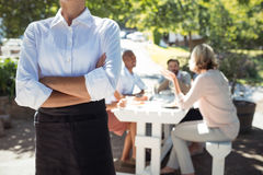 Waitress standing with arms crossed in restaurant Stock Photos