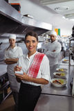 Waitress standing with kitchen staff in commercial kitchen Royalty Free Stock Photos
