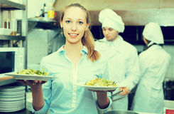 Waitress taking dish from kitchen. Smiling blonde young waitress taking dish from kitchen royalty free stock images