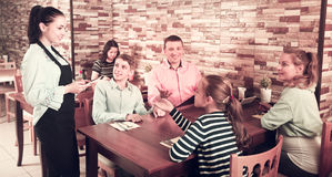 Waitress taking order from guests. Young waitress taking order from guests and writing into note Stock Images