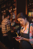 Waitress taking an order on notepad at counter. In pub Royalty Free Stock Image