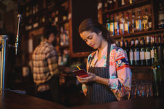 Waitress taking an order on notepad at counter. In pub Royalty Free Stock Photography