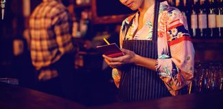 Waitress taking an order on notepad at counter. In pub Stock Image