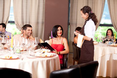 Waitress taking the order from restaurant table. Waitress taking dinner order restaurant table young couple Royalty Free Stock Photography