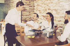 Waitress taking order at table of people Royalty Free Stock Photo