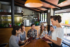 Waitress taking orders from customers in restaurant. Young waitress taking orders from customers in restaurant Stock Photos