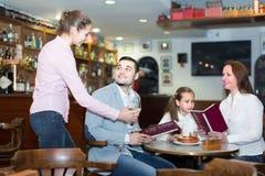 Waitress taking table order at cafe Royalty Free Stock Photos