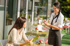 Waitress taking woman's order at cafe bar Stock Photography