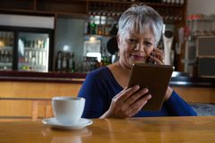 Waitress talking on his phone. Near cafe counter Royalty Free Stock Photography