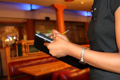 Waitress tending to the orders of her customers Royalty Free Stock Images
