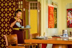 Waitress in the thai restaurant with teapot and cup making tea royalty free stock photography