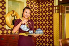Waitress in the thai restaurant with teapot and cup royalty free stock photos