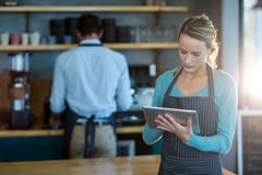Waitress using digital tablet at counter. In caf Stock Image