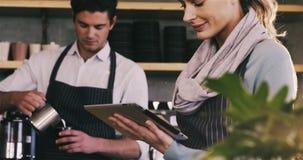 Waitress using digital tablet at counter. In café 4k stock video