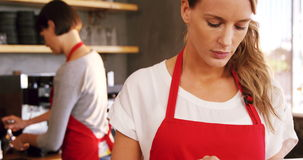 Waitress using digital tablet at counter stock video footage