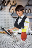 Waitress using digital tablet with glass of cocktail in bar counter Royalty Free Stock Image