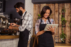 Waitress using digital tablet while waiter preparing coffee in background Stock Photos