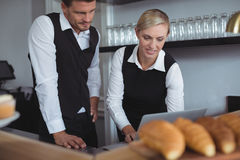 Waitress using laptop at counter Royalty Free Stock Images