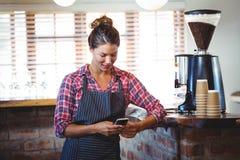 Waitress using a smartphone Stock Photos