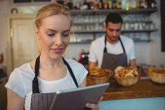 Waitress using tablet computer with colleague in background. At cafeteria Stock Photos