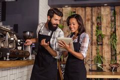 Waitress using a tablet computer and waiter with coffee machine Stock Photography