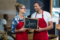 Waitress and waiter standing with open sign board in café Royalty Free Stock Photography