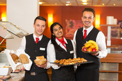 Waitress and waiters posing with food at buffet in a restaurant Stock Photography