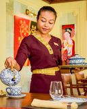 Waitress wearing uniform in the thai restaurant serving tea. Waitress wearing traditional uniform clothes in the thai restaurant serving tea in Maldives stock images