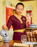 Waitress wearing uniform in the thai restaurant serving tea stock images