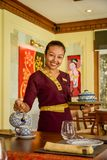 Waitress wearing uniform in the thai restaurant serving tea with a smile. Waitress wearing traditional uniform clothes in the thai restaurant serving tea with a stock photo