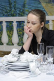 Waitress at work. Waitress wondered at the table with dirty dishes Stock Image