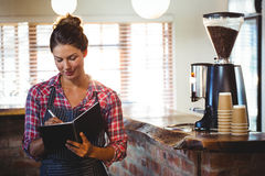 Waitress writing in a book Royalty Free Stock Images