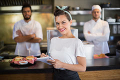 Waitress writing while chef standing in kitchen. Portrait of waitress writing while chef standing in kitchen stock photo