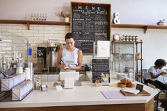 Waitress writing customer�s order at counter of coffee shop Royalty Free Stock Photography