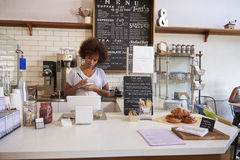 Waitress writing down an order at the counter of coffee shop Stock Image