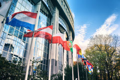 Waiving flags in front of European Parliament building. Brussels Stock Image