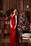 Wakacje, świętowanie i ludzie pojęć, - młoda uśmiechnięta kobieta w eleganckiej czerwieni sukni nad bożego narodzenia wnętrza tłe Fotografia Stock