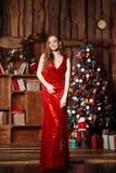 Wakacje, świętowanie i ludzie pojęć, - młoda uśmiechnięta kobieta w eleganckiej czerwieni sukni nad bożego narodzenia wnętrza tłe Zdjęcia Stock