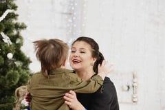 Wakacje, boże narodzenia, miłość i szczęśliwa rodzina, Chłopiec całowania matka Obraz Stock