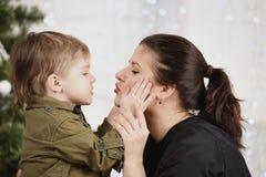 Wakacje, boże narodzenia, miłość i szczęśliwa rodzina, Chłopiec całowania matka Zdjęcie Stock