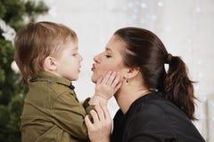 Wakacje, boże narodzenia, miłość i szczęśliwa rodzina, Chłopiec całowania matka Obrazy Stock