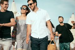 wakacje, wakacje grupa przyjaciele ma zabawę na plaży, odprowadzenie, napoju piwo ono uśmiecha się i ściska, fotografia stock