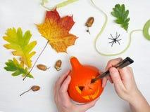 Wakacje, Halloween, dekoracja i ludzie pojęć, - zakończenie up kobiet ręki z banią na białym drewnianym tle Obrazy Stock