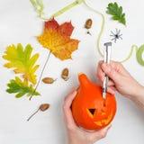Wakacje, Halloween, dekoracja i ludzie pojęć, - zakończenie up kobiet ręki z banią na białym drewnianym tle Obrazy Royalty Free