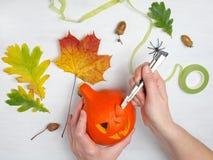 Wakacje, Halloween, dekoracja i ludzie pojęć, - zakończenie up kobiet ręki z banią na białym drewnianym tle Zdjęcie Royalty Free