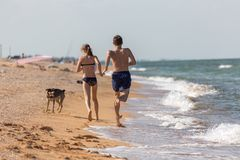 Wakacje, letni dzień na plaży przy morzem kilka nastolatkowie baraszkują i biegają na mokrym piasku obraz stock