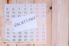 Wakacje pisać na papier notatce na ściennym kalendarzu zdjęcie stock