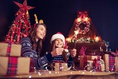 Wakacje, rodzina i ludzie pojęć, Szczęśliwa matka i mała dziewczynka w Santa pomagiera kapeluszu z sparklers w rękach, prezent zdjęcia royalty free